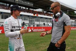 Nico Rosberg, Mercedes AMG F1 y Daniel Schloesser, Mercedes AMG F1 Physio en la parrilla