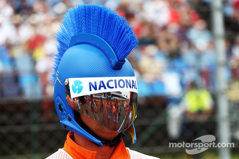 A marshal with a mohican Ayrton Senna themed helmet.