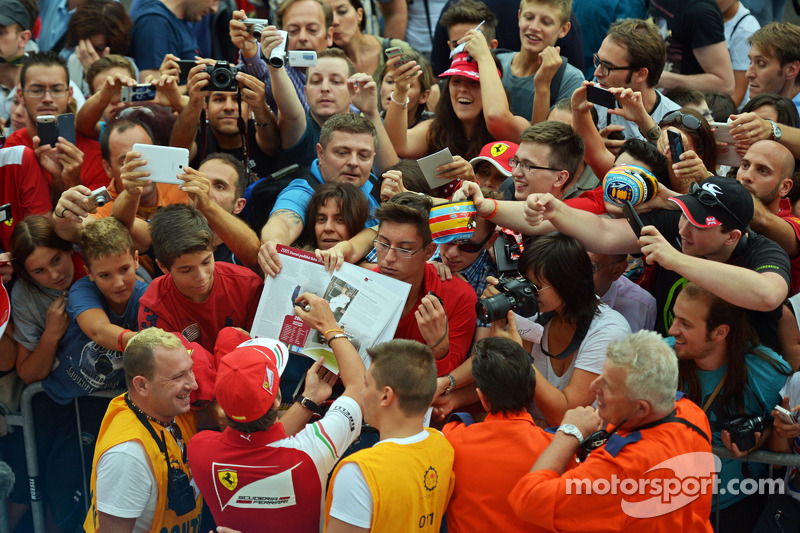Fernando Alonso, Ferrari signs autographs for the fans in the pit lane