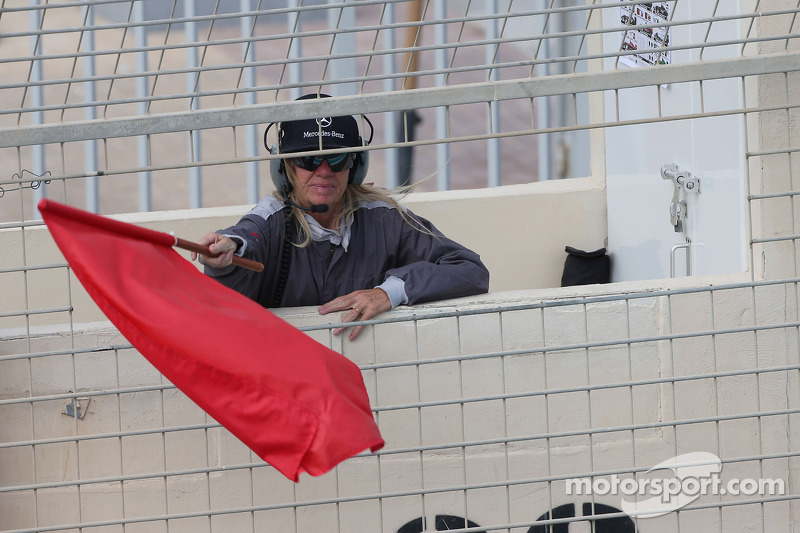 A marshal waves a red flag