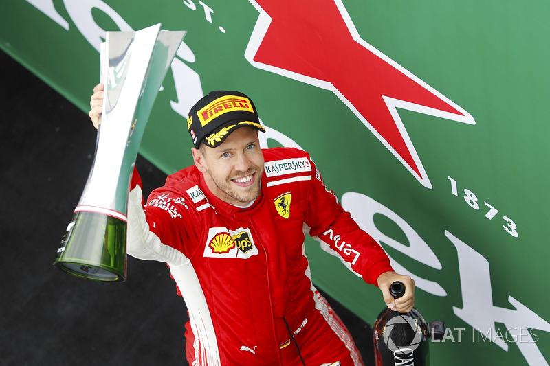 Sebastian Vettel, Ferrari, raises his winner's trophy on the podium