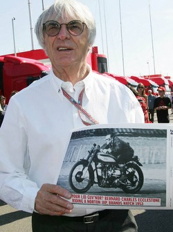 Bernie Ecclestone holds a picture of himself on a motorbike in 1953