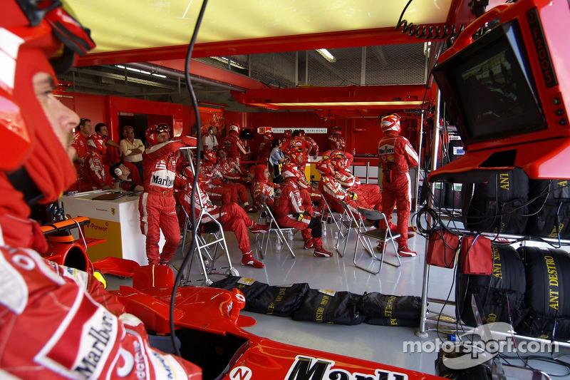 Los miembros del equipo Ferrari esperan para la siguiente parada en boxes