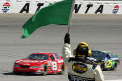 An official waves the green flag as Dale Earnhardt Jr. and Brian Vickers pass