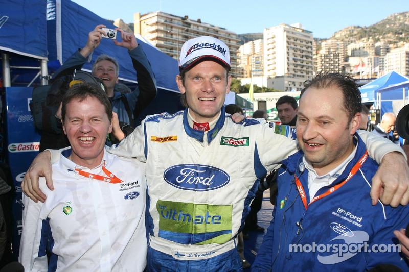 Переможець Маркус Грьонхольм святкує з Малкольмом Вілсоном і головним конструктором Крістіаном Лоріо