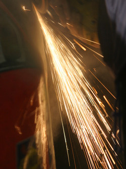 Sparks fly as Tide Chevy crew members repair the #32 car