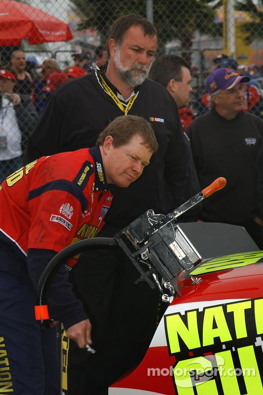 Un équipier ajuste l'aileron sur la voiture NASCAR lors de l'inspection