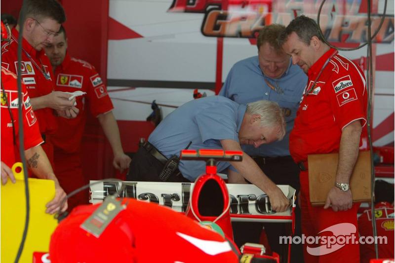 FIA technical delegates inspect the Ferrari