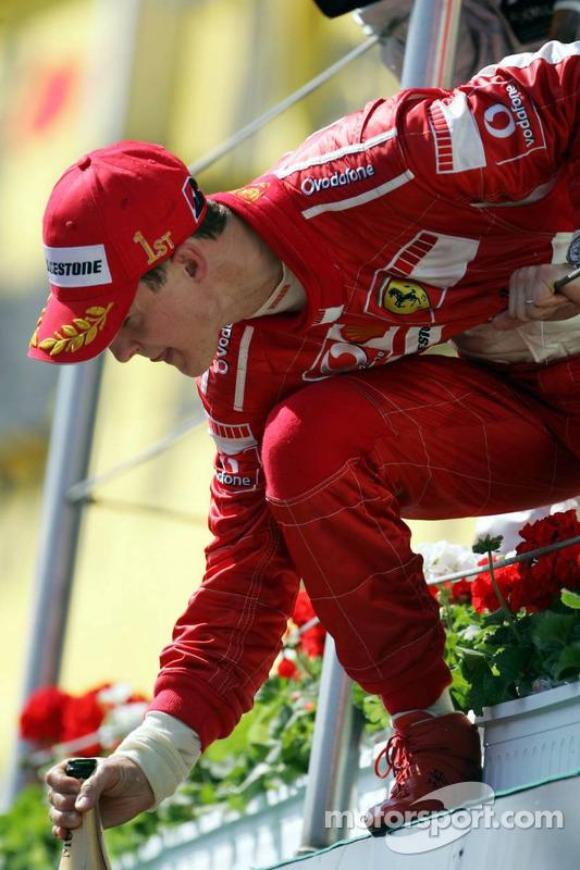 Michael Schumacher verse une bouteille de champagne sur son équipe