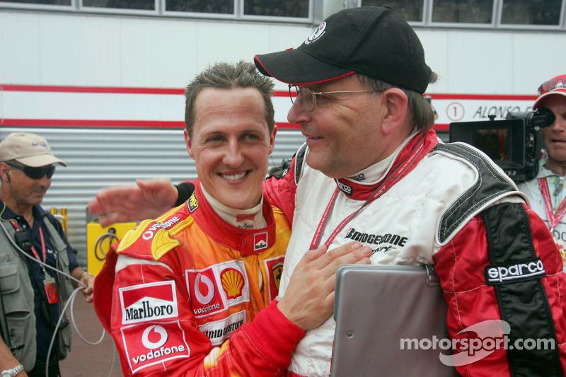 Michael Schumacher celebra con Kees van de Grint, Ingeniero de neumáticos de Bridgestone