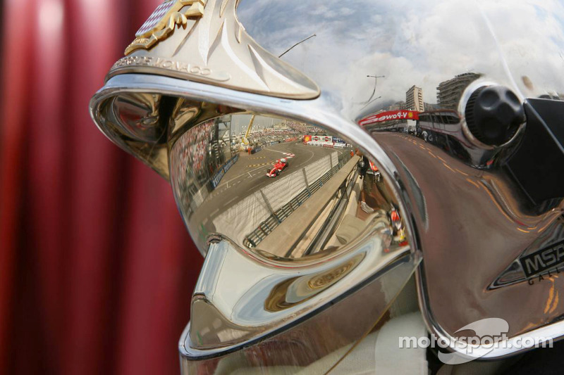Un commissaire regarde passer Michael Schumacher