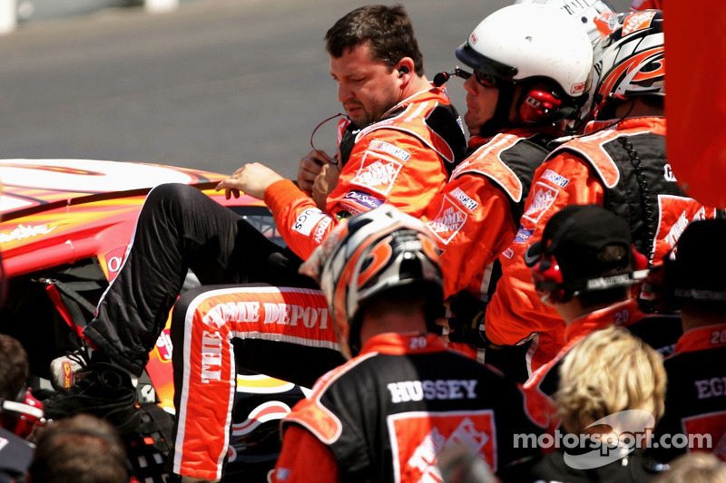 Des membres d'équipe assistent Tony Stewart pour monter dans la No. 20 Home Depot Chevrolet