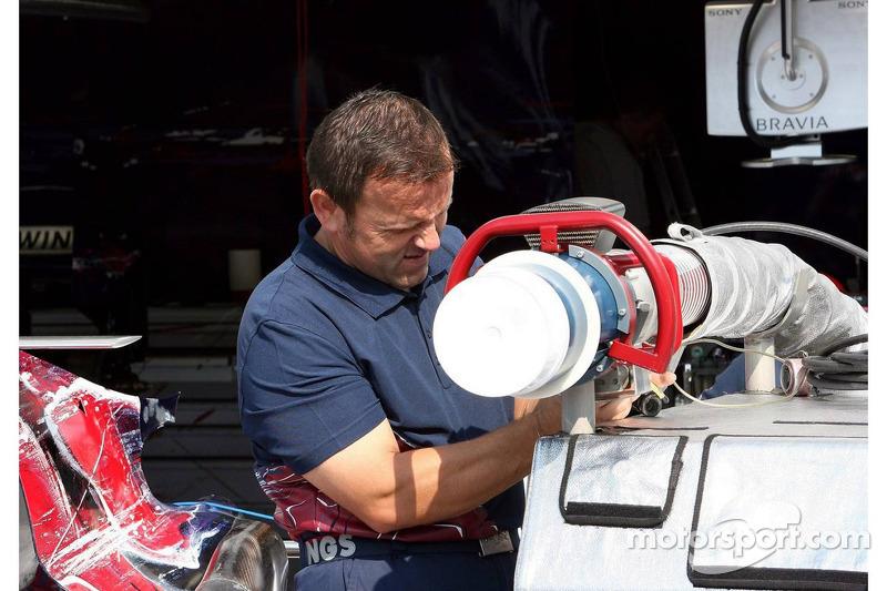 Un membre de l'équipe Scuderia Toro Rosso prépare les plates-formes de carburant