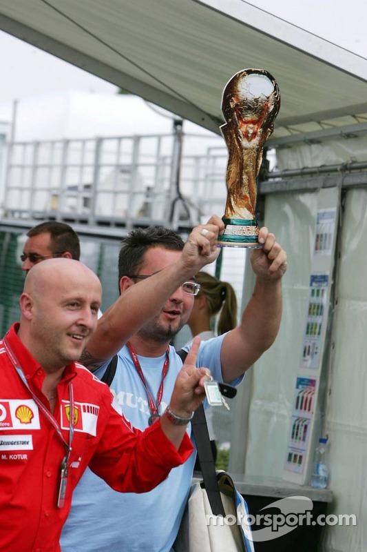 Des membres de l'équipe italianne Ferrari entrent dans le paddock brandissant une reproduction du trophée de la Coupe du monde