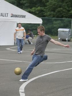 Adam Carroll plays football in the paddock