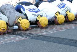 Race winner Jimmie Johnson kisses the bricks with Lowe's Chevy crew members