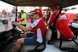 Себастьян Феттель, Ferrari ведет гольф-кар с Кими Райкконеном, Ferrari и Бриттой Роеске, пресс-секре