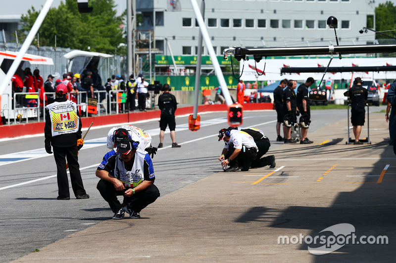 Debris is cleared from the pit lane