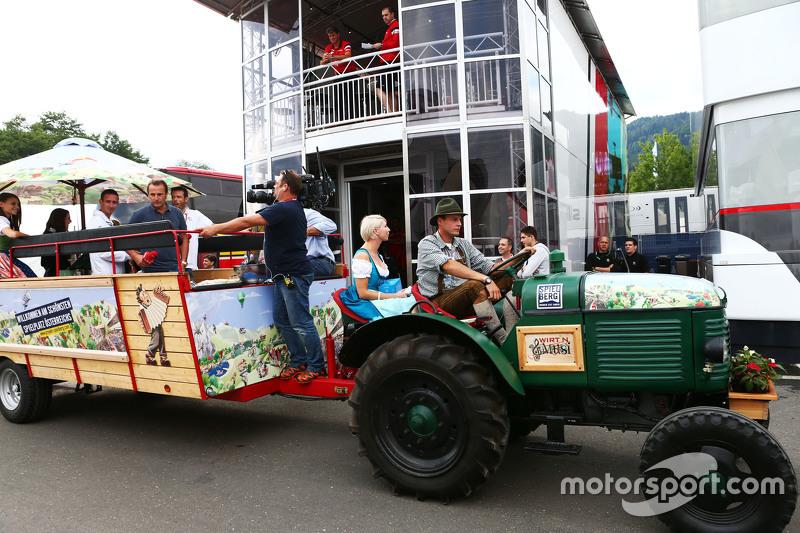 Sebuah traktor lokal Spielberg menderek bak di depan motorhome Manor F1 Team