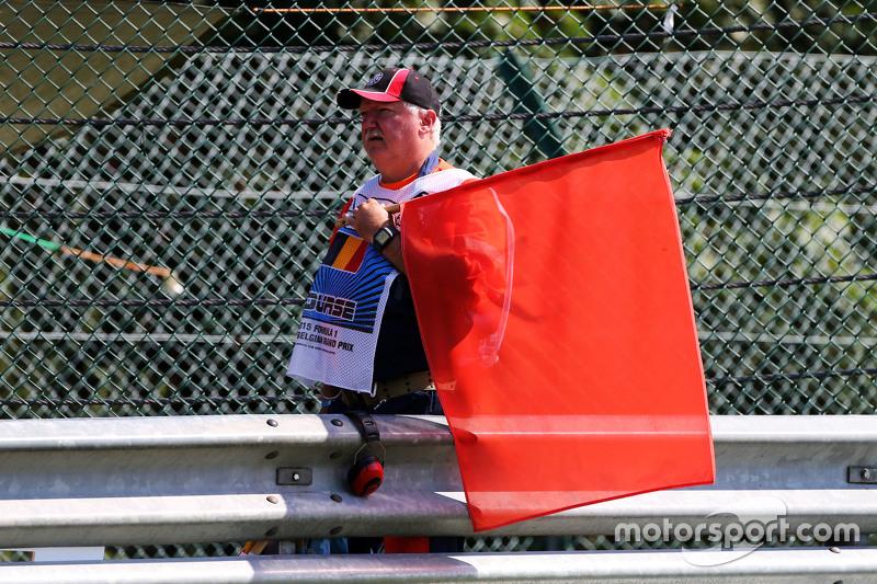 Seorang marshal dengan bendera merah