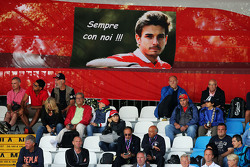 Aficionados en la tribuna principal con una bandera para Jules Bianchi