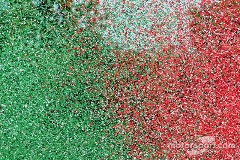 Miles de papelitos con los colores de la badera de italia en el podio