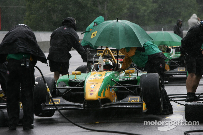 Will Power sits in his car as the rain falls heavily
