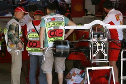 Scrutineers in the Scuderia Ferrari garage