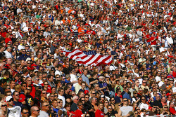Race fans hold the flag in the grandstands