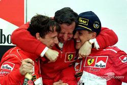 Podio: ganador de la carrera Michael Schumacher y Eddie Irvine de segundo lugar celebran con Jean To