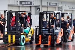 Los mecánicod de Lotus F1 Team con carretillas elevadoras