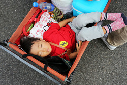 A young fan sleeps in a trolley
