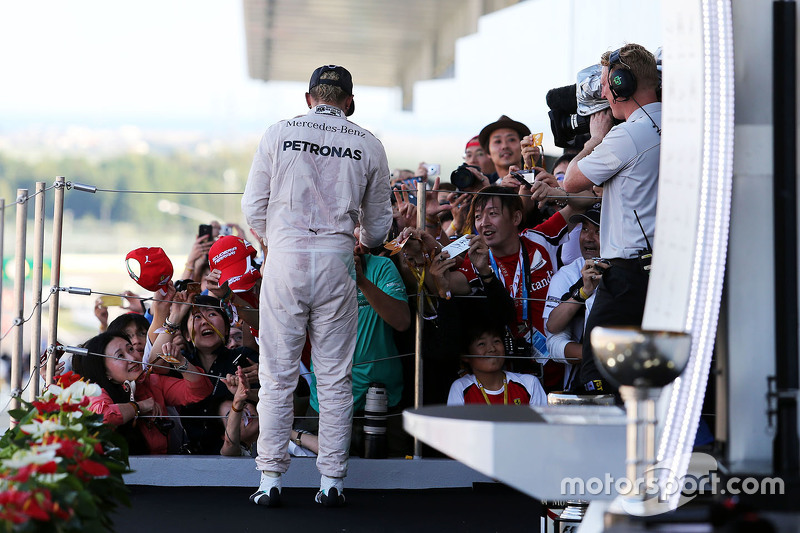 Race winner Lewis Hamilton, Mercedes AMG F1 signs autographs for the fans on the podium