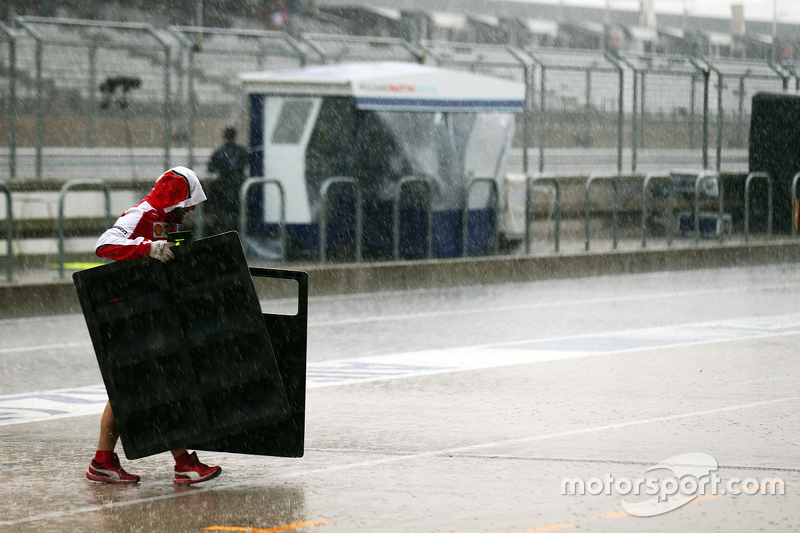 A Ferrari mechanic in the pits during a thunderstorm that cancelled FP2