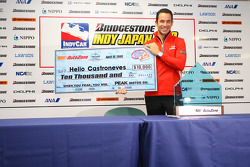 Helio Castroneves with the pole winner check