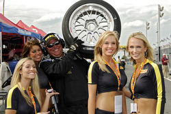 A crew member displays a Pirelli tire with the Pirelli girls in pit lane