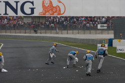 Corner workers clean up the track