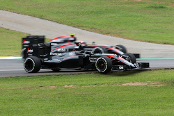 Jenson Button, McLaren MP4-30 passes the stricken McLaren MP4-30 of team mate Fernando Alonso, McLaren in the second practice session