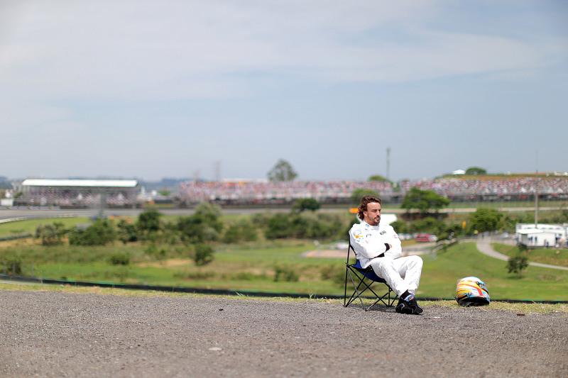Fernando Alonso observa la clasificación sentado en una silla a un lado del circuito después de abandonar