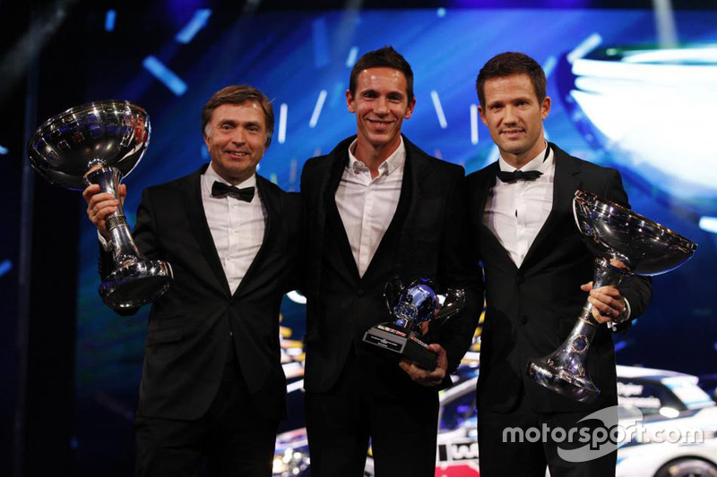 Sebastien Ogier and his co-driver Julien Ingrassia claim the WRC champion's trophy for the third year in succession, joined by VW boss Jost Capito.