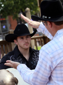 Former four-time bull riding champion Tuff Hedeman gives NASCAR Sprint Cup Series driver Scott Speed some bull riding tips in the Fort Worth Stockyards