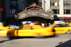 Taxis race through Times Square in New York City Wednesday in front of the Hard Rock Cafe's marquee with a Tissot countdown clock counting down to the start of Tailgate City driven by Ford