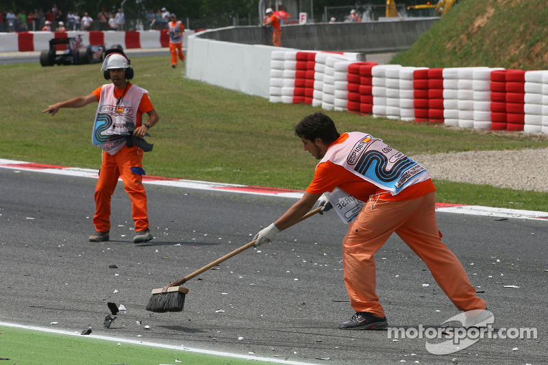 Marshalls cleaning the track after the crash