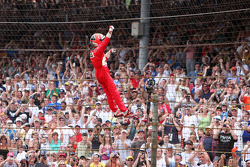 Race winner Helio Castroneves climbs the fence