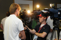 Marcus Gronholm gives TV interviews at a Wednesday press conference after the first practice session
