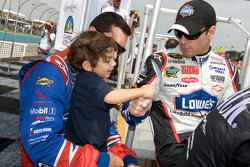 Jimmie Johnson, Hendrick Motorsports Chevrolet, shakes hand with the kid of Max Papis, Germain Racing Toyota