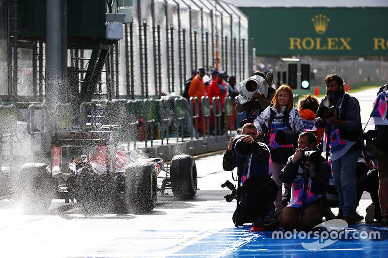 Fotógrafos preparados, enquanto que Max Verstappen levanta água na área dos pits