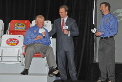 Team owner Joe Gibbs tries out a new seat with Marcus Smith and J. D. Gibbs observing