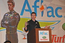 Carl Edwards addresses the media with his familiar Aflac duck logo in background