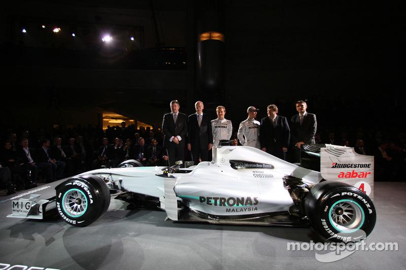 Ross Brawn, Dr. Dieter Zetsche, Nico Rosberg, Michael Schumacher, Norbert Haug et  Nick Fry posent avec la Brawn GP de 2009 décorée de la nouvelle livrée 2010